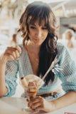 Jonge donkerbruine vrouw die een glas roomijs eten stock afbeeldingen