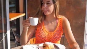 Jonge Donkerbruine Vrouw die een Koffiezitting in een Koffie op de Straat drinken stock videobeelden