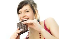 Jonge donkerbruine vrouw die een reep chocolade eet Stock Afbeelding
