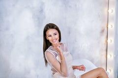 Jonge Donkerbruine vrouw die met rechte en zijdeachtige haarzitting voor spiegel op grijze achtergrond op de linkerzijde en het g Royalty-vrije Stock Fotografie
