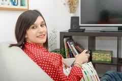 Jonge donkerbruine vrouw die op TV letten, die op de bank zitten royalty-vrije stock fotografie