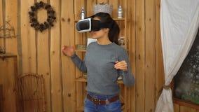 Jonge donkerbruine vrouw die vr glazen thuis gebruiken stock videobeelden