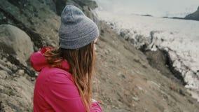 Jonge donkerbruine vrouw die zich op de berg bevinden en op gletsjers in Vatnajokull-ijslagune kijken in IJsland stock video