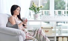 Jonge donkerbruine vrouw het drinken thee Royalty-vrije Stock Afbeelding