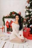 Jonge donkerbruine vrouw in Kerstmisbinnenland stock foto's