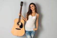 jonge donkerbruine vrouw met gitaar in handen Royalty-vrije Stock Fotografie