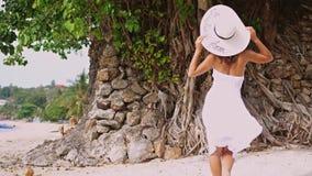 Jonge donkerbruine vrouw met lang haar in witte drees en hoed die op een tropisch strand lopen Langzame Motie 3840x2160 stock footage
