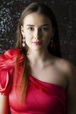 Jonge donkerbruine vrouw op de donkere achtergrond van de studiomuur Stock Afbeelding