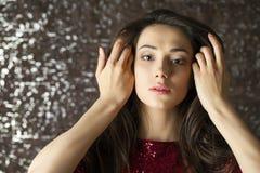 Jonge donkerbruine vrouw op de donkere achtergrond van de studiomuur Stock Foto's