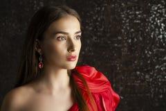 Jonge donkerbruine vrouw op de donkere achtergrond van de studiomuur Royalty-vrije Stock Foto