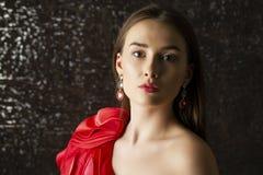 Jonge donkerbruine vrouw op de donkere achtergrond van de studiomuur Royalty-vrije Stock Foto's