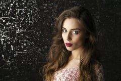 Jonge donkerbruine vrouw op de donkere achtergrond van de studiomuur Stock Fotografie