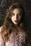 Jonge donkerbruine vrouw op de donkere achtergrond van de studiomuur Royalty-vrije Stock Fotografie