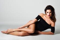 Jonge donkerbruine vrouw in zwarte lingerie die op de vloer liggen Royalty-vrije Stock Foto