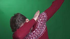 Jonge donkerbruine zakenman in sweater synchroniseren die gelukkig en blij op groene achtergrond zijn stock videobeelden