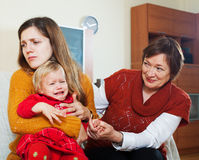 Jonge droefheidsmoeder met schreeuwende baby en grootmoeder Royalty-vrije Stock Foto
