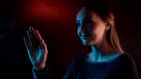 Jonge droevige dromerige vrouw dichtbij vochtig glasvenster wat betreft tekeningshart in het blauwe neonlicht en kindmeisje achte stock videobeelden