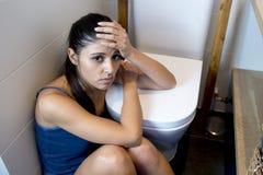 Jonge droevige en gedeprimeerde boelimische vrouw die zieke zitting voelen bij de vloer van het toilet die op WC leunen stock foto's