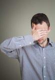 Jonge droevige mens die zijn gezicht met hand verbergen Stock Afbeeldingen