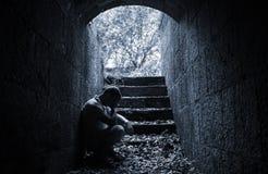 Jonge droevige mensenzitting binnen van donkere steentunnel Royalty-vrije Stock Afbeelding