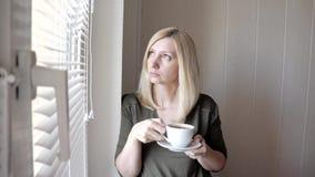 Jonge droevige thinkful mooie blonde vrouw die zich dichtbij het venster met zonneblinden in de ochtend en het drinken koffie bev stock videobeelden