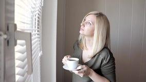 Jonge droevige thinkful mooie blonde vrouw die zich dichtbij het venster met zonneblinden in de ochtend en het drinken koffie bev stock video