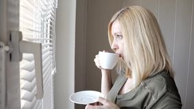 Jonge droevige thinkful mooie blonde vrouw die zich dichtbij het venster met zonneblinden in de ochtend en het drinken koffie bev stock footage