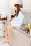 Jonge droevige vrouwenzitting op keukenteller Stock Afbeelding