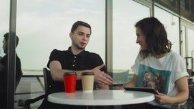 Jonge echtpaar met tabletcomputer in café Vrouw die iets laat zien aan de man en ze hebben een levendig gesprek stock videobeelden