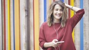 Jonge eerlijke haarvrouw die een rode sweater dragen die zich dichtbij een kleurrijke muur bevinden die aan de muziek met haar ho royalty-vrije stock foto