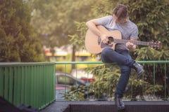 Jonge elegante mens die een gitaar op een openluchtgebied spelen in de voorsteden royalty-vrije stock foto