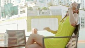 Jonge elegante vrouw die op vriend op terras dichtbij zwembad wachten Stadslandschap op achtergrond stock videobeelden