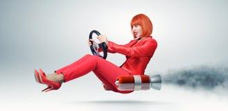Jonge elegante vrouw in rode bestuurdersauto met een wiel Stock Foto's