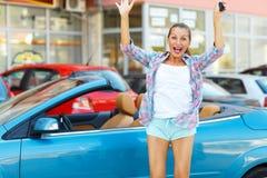 Jonge emotionele vrouw die zich dichtbij convertibel met de sleutels bevinden Royalty-vrije Stock Foto's