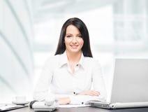 Jonge en aantrekkelijke bedrijfsvrouw die in bureau werken Stock Foto's