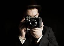 Jonge en aantrekkelijke fotograaf in uitstekend kostuum en met retro fotocamera stock foto