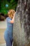 Jonge en elegante vrouw in gestripte kleding dichtbij rots stock fotografie