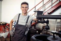 Jonge en gekwalificeerde automechanic glimlacht terwijl op het werk tijdens een korte onderbreking royalty-vrije stock foto's