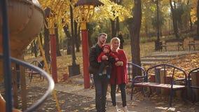 Jonge en gelukkige familie met een baby in de speelplaats schommeling en carrousels in het park stock footage