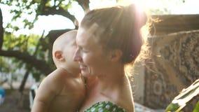 Jonge en gelukkige moeder die haar baby in de zomer op de aard in openlucht houden Het jonge geitje kust onhandig zijn moeder, stock footage