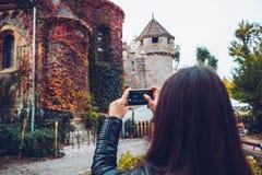 Jonge en gelukkige toeristenvrouw die foto van oud kasteel maken stock afbeeldingen