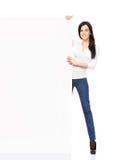 Jonge en gelukkige vrouw die in jeans een banner houden Stock Afbeelding