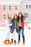 Jonge en gelukkige vrouwen die in openlucht in de winter schaatsen Stock Fotografie