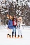 Jonge en gelukkige vrouwen die in openlucht in de winter schaatsen stock afbeelding