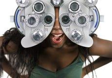 Jonge en gelukkige zwarte afro Amerikaanse vrouw die bij het ziekenhuis door optometrisch het ziekenhuisapparaat kijken die ogen  stock foto's