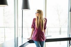 Jonge en glimlachende uitvoerende vrouw die zich voor het heldere venster bevinden Royalty-vrije Stock Afbeelding