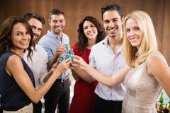 Jonge en knappe groep vrienden die schoten drinken stock fotografie