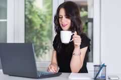 Jonge en leuke bedrijfsvrouw die aan laptop werken en kop van koffie houden royalty-vrije stock afbeeldingen