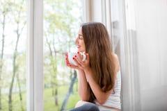 Jonge en leuke damezitting op de vensterbank en het kijken uit Th Royalty-vrije Stock Foto