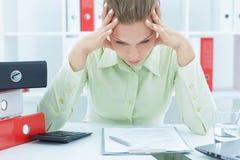 Jonge en mooie die onderneemster van het werk in het bureau wordt vermoeid Stock Foto's